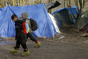 Migrant children make their way past shelters in a muddy field called the Grande-Synthe jungle near Dunkerque