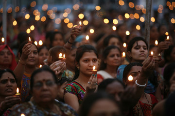 People hold lamps as they pray to the Hindu god Vishwakarma to celebrate his birthday at a temple in the western Indian city of Ahmedabad