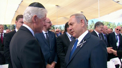 A still image from a video showing former U.S. President Bill Clinton greeting Israel's PM Netanyahu at funeral of former Israeli President Peres in Jerusalem