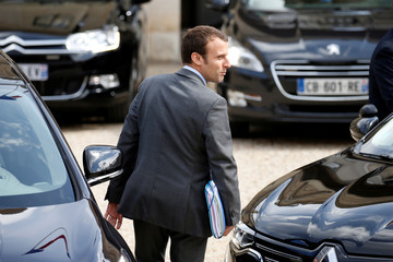 French Economy Minister Emmanuel Macron leaves the Elysee Palace after the weekly cabinet meeting in Paris