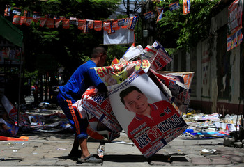 A government worker carries candidates' campaign posters during their clean-up operations a day after a national elections at Manila in the Philippines