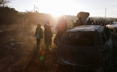 Relatives and civilians stand in the smoke as they look at the wreckages of cars burnt after a fireball from an tanker engulfed several vehicles and killed several people, near the Rift Valley town of Naivasha, west of Kenya's capital Nairobi