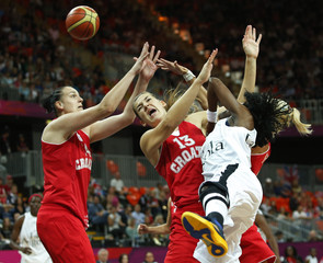 Angola's Catarina Camufal loses possession of the ball against Croatia's Luca Ivankovic and Croatia's Mirna Mazic during their women's basketball preliminary round, Group A match at the Basketball Arena during the London 2012 Olympic Games