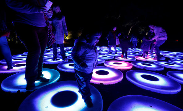 """A child interacts with """"Luminous Lawn"""" which is part of the exhibit """"Enchanted: Forest of Light"""" at Descanso Gardens in La Canada Flintridge"""