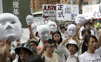 Activists holding masks take part in a protest in front of the Japan Interchange Association in Taipei