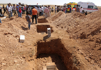Three graves that were dug for the two Syrian toddlers and their mother, are pictured during their funeral at the border town of Kobani