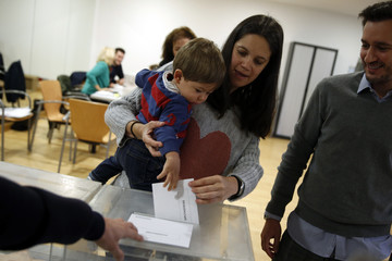 A boy votes with his mother in Spain's general election at a polling station in Pozuelo de Alarcon