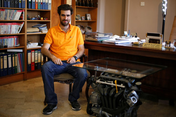 Jordanian graphic designer Abdelrahman Asfour, who turns car parts into furniture, poses next to one of his products at a customer's office in Amman