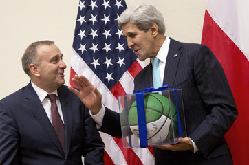 U.S. Secretary of State Kerry gives a basketball as a gift to Poland's FM Schetyna in Brussels