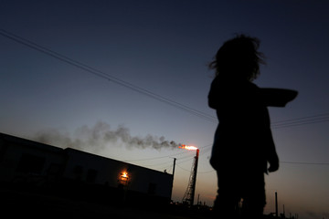 A child stands in front of her house as the Cardon refinery, which belongs to the Venezuelan state oil company PDVSA, is seen in the background in Punto Fijo