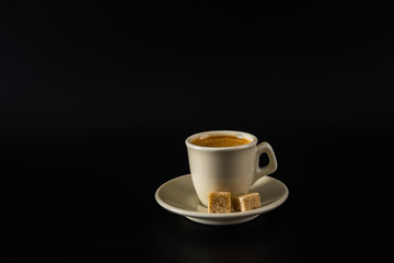 aromatic black coffee in a white cup, brown sugar,black background, drink set