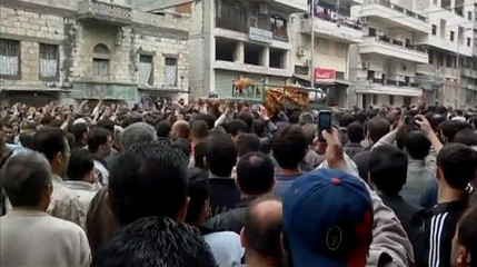 A still image from an amateur video shows mourners watching as coffin of recent victim of clashes is carried through streets of Banias