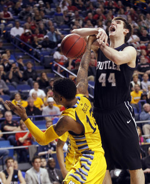Butler University's Andrew Smith fights to get his shot off under pressure from Marquette University's Vander Blur during their third round NCAA basketball game in Lexington