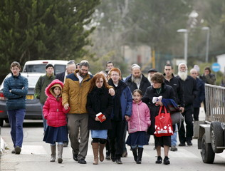 The husband and children of Meir walk together upon their arrival to her funeral ceremony in the West Bank Jewish settlement of Otniel