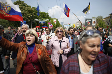 Participants shout slogans and wave Russian flags during an International Worker's Day, or Labour Day, parade in Donetsk