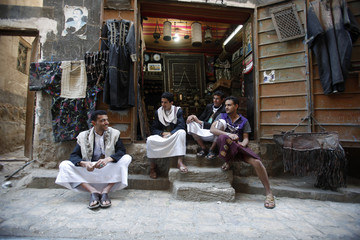 People sit outside a shop in the Old Sanaa city