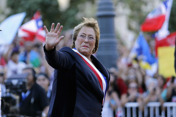 Chile's new president Michelle Bachelet waves to the crowd as she arrives at the La Moneda presidential palace after being sworn into office, in Santiago