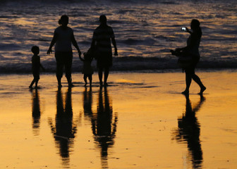 People take pictures with a mobile phone after sunset at Moonlight Beach in Encinitas, California