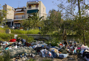 Potev, a 56-year-old Bulgarian immigrant, lies on a mattress amid garbage in an Athens suburb