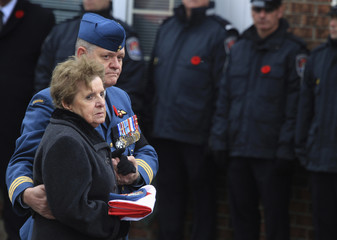 Guerette Vincent, mother of Warrant Officer Patrice Vincent, holds her son's cap and medals with the Canadian flag that adorned his coffin following his funeral in Longueuil, Quebec
