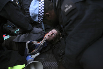 Police arrest an Occupy London protestor on the roof of Panton House, a building used by mining company Xstrata, in central London