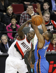 Crawford passes against Westbrook during NBA basketball game in Portland