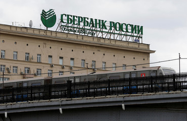 Metro train moves on bridge with logo of Sberbank on top of building seen in background in Moscow