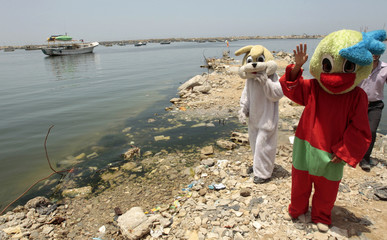 Palestinians wearing costumes take part in a protest at Gaza's seaport