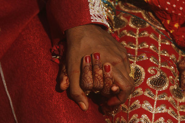 A bride and groom hold hands as they sit together during a mass marriage ceremony held in Karachi