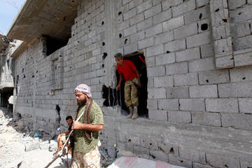 Fighter of Libyan forces allied with the U.N.-backed government walks out of a hole in a house near the frontline of fighting with Islamic State militants, in Cambo area in Sirte