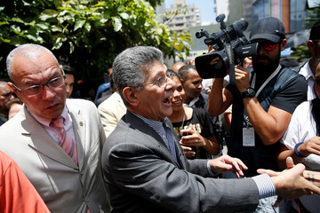 Henry Ramos Allup, President of the National Assembly and deputy of the Venezuelan coalition of opposition parties, greets supporters as he arrives to the hearing of Venezuelan opposition leader Leopoldo Lopez at a courthouse in Caracas