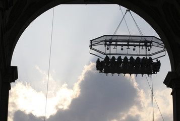 """Guests enjoy a """"Dinner in the Sky"""" on a platform hanging in front of the Cinquantenaire park in Brussels"""