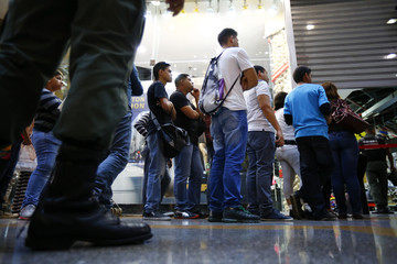 People wait in line to enter a store having sales as a member of the national guard patrols, at a mall in Caracas