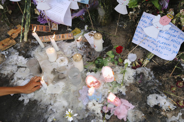 A resident lights candles in memory of the children who died in a burning bus, at the site of the accident in Fundacion, northern Colombia