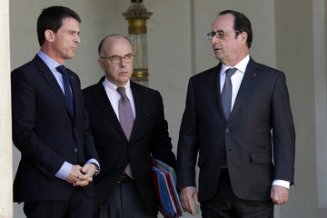 French President Hollande speaks with Interior minister Cazeneuve and Prime Minister Valls at the Elysee Palace in Paris