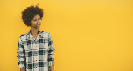 Teenage black model in casual outfit pensively looking aside while standing in front of yellow background, serious young Brazilian girl in plaid shirt with copy space for text, logo or advertising