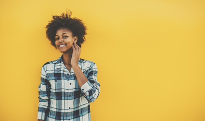 Young biracial student girl with perfect smile and curly afro hair in casual checkered outfit staying in front of solid yellow wall and touching her face, with copy space place for your advertising