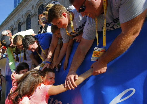 2013 Boston Marathon survivors Sydney Corcoran and her mother Celeste are hugged by friends and family after crossing the finish line with Celeste's sister Acabbo, who ran the 118th Boston Marathon in Boston