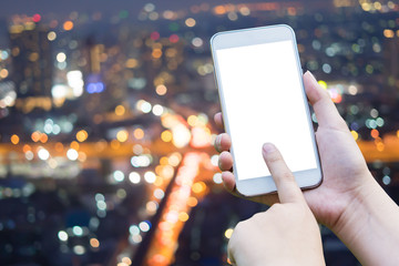 woman hand holding,using and touch smart phone,cell phone,mobile over blurred image of  night light city scape bokeh background