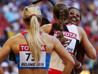 Sharika Nelvis of the U.S. (R) hugs Noemi Zbaren of Switzerland after competing in the women's 100 metres hurdles heats during the 15th IAAF World Championships at the National Stadium in Beijing