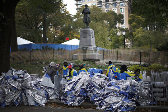 Volunteers pile space blanket warming sheets for finishing runners past the finish line shortly before the start of the 2014 New York City Marathon in Central Park in Manhattan