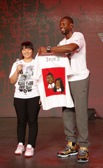 NBA Miami Heat's Wade laughs as he receives a shirt from a fan with a cartoon painting of him and his girlfriend Union during a promotional event for Li Ning's Way of Wade sneakers, in Beijing