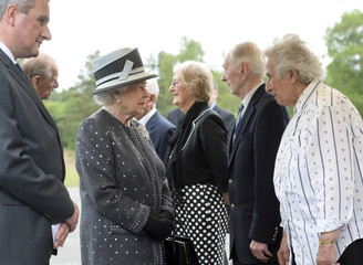 Britain's Queen Elizabeth and Prince Philip speak with Levy, Capt. Brown and Lasker-Wallfisch during a visit to the site of the former Nazi concentration camp Bergen-Belsen