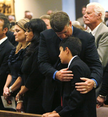 John Green hugs his son Dallas as grandfather Dallas Green stands in the background at the funeral mass for Christina Green in Tucson