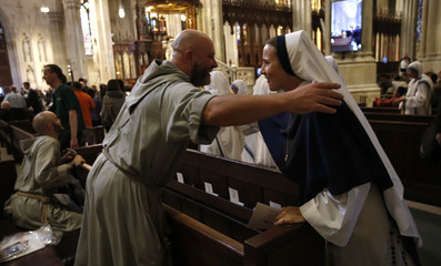 A nun and a friar greet each other ahead of Pope Francis' celebration of evening prayers at St. Patrick's Cathedral in New York