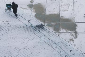 A worker de-ices a frozen sidewalk as snow falls in Boston, Massachusetts