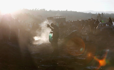 A man walks in the smoke as they assess the wreckages of cars burnt after a fireball from an tanker engulfed several vehicles and killed several people, near the Rift Valley town of Naivasha, west of Kenya's capital Nairobi