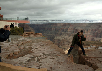 Tourists pose for pictures near an unfinished building housing a glass skywalk, overlooking the Grand Canyon and the Colorado River below, on the Hualapai Indian Reservation, Arizona