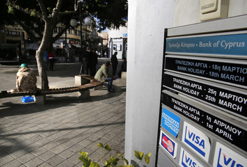 People sit outside bank in Nicosia