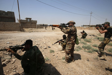 Asaib Ahl al-Haq Shi'ite militia fighters from the south of Iraq and Kurdish peshmerga forces take control of Sulaiman Pek from the Islamist State militants, in the northwest of Tikrit city